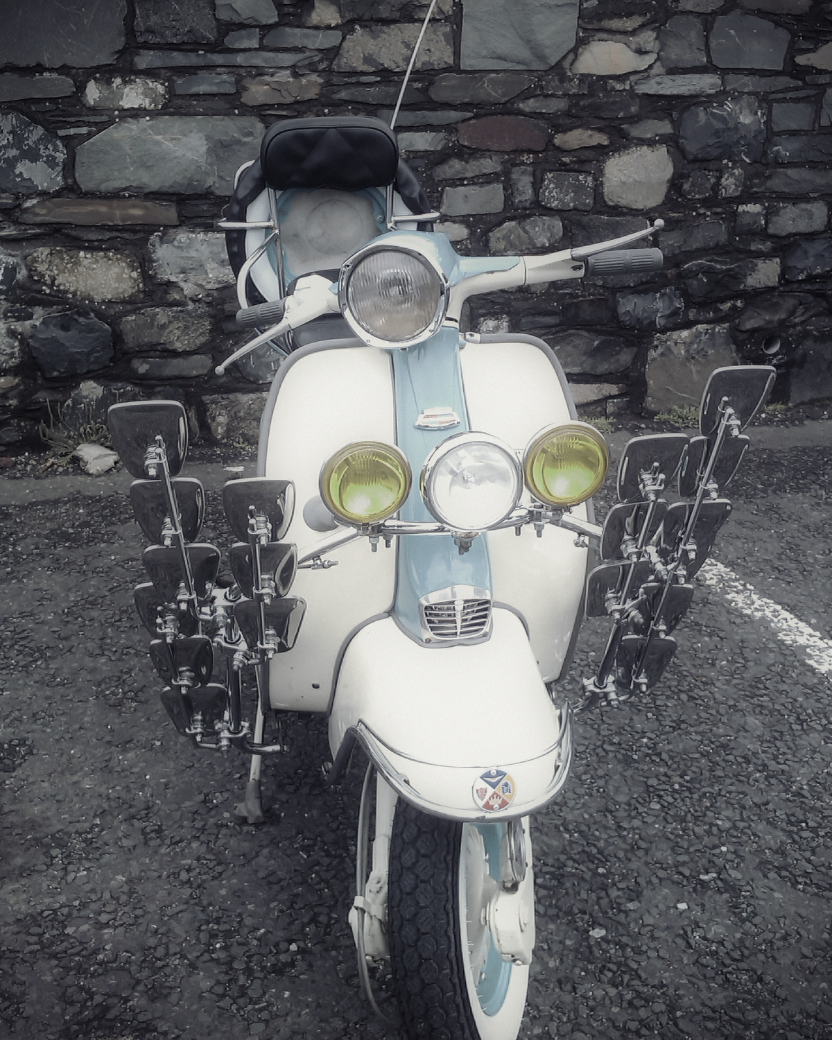 A small scooter covered in silvery rear-view mirrors, Portpatrick harbour
