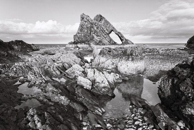 A classic view - the strong angular shape of Bow Fiddle with rock-pools in the foreground, Portknockie.