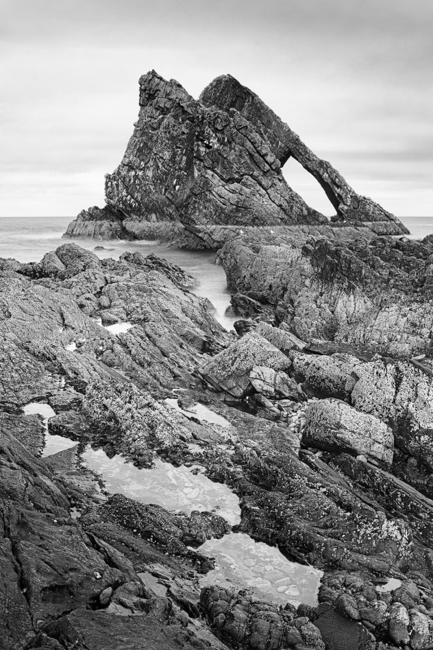 A classic view - the strong angular shape of Bow Fiddle with rock-pools in the foreground, Portknockie.This was a real blighter of a shot to make. Even with the tripod legs not very extended and wedged into crevices in the rockpool, the wind was such that even a few seconds' exposure was impossible. Added to this, the light seen here was so transient, it blossomed to optimum golden-yellow on the stone and vanished again within the course of about 10 seconds.Black+white conversion: Ilford PanF-50+ simulation in the Gimp.