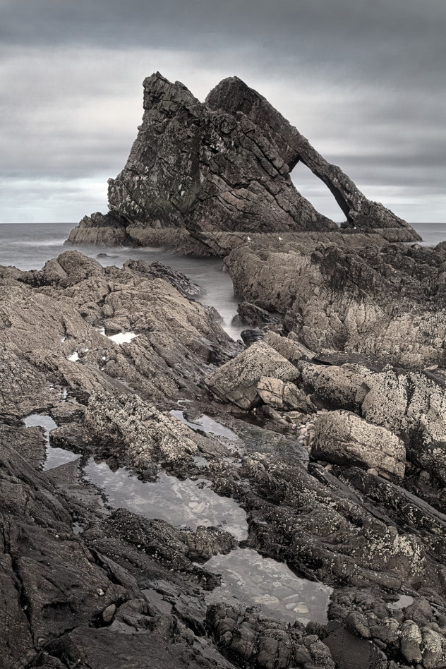 A classic view - the strong angular shape of Bow Fiddle with rock-pools in the foreground, Portknockie.I quite like it in this semi-desaturated rendition; it seems to bring a melancholy mood to the scene, not entirely unrealistic.