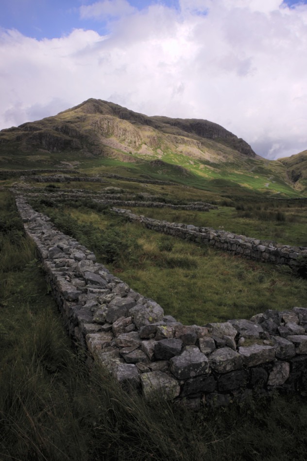 Sunlight on the hills; just one small corner of an ancient Roman stone wall in the fort at Mediobogdum on Hardknott Pass.