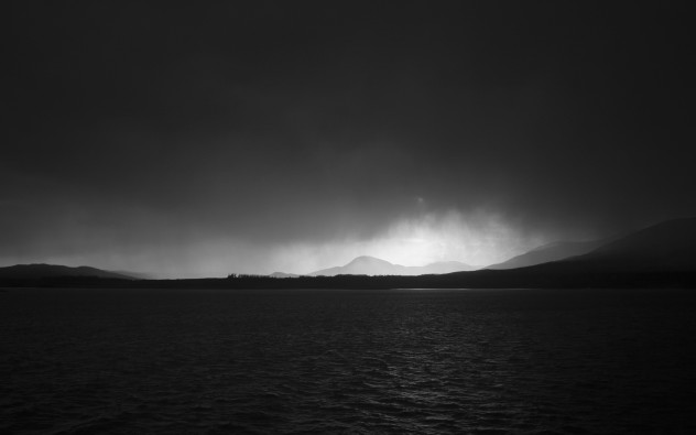 Beautiful sunlight illuminating heavy precipitation, light subtly reflecting on the water, on the approach to Craignure.