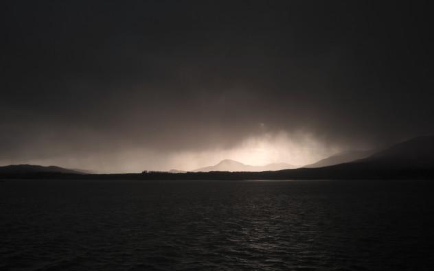 Beautiful sunlight illuminating heavy precipitation, light subtly reflecting on the water, on the approach to Craignure.