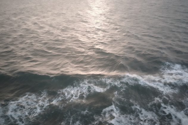 Detail of soft sunlight reflecting on the sea and bow-waves from the ferry.