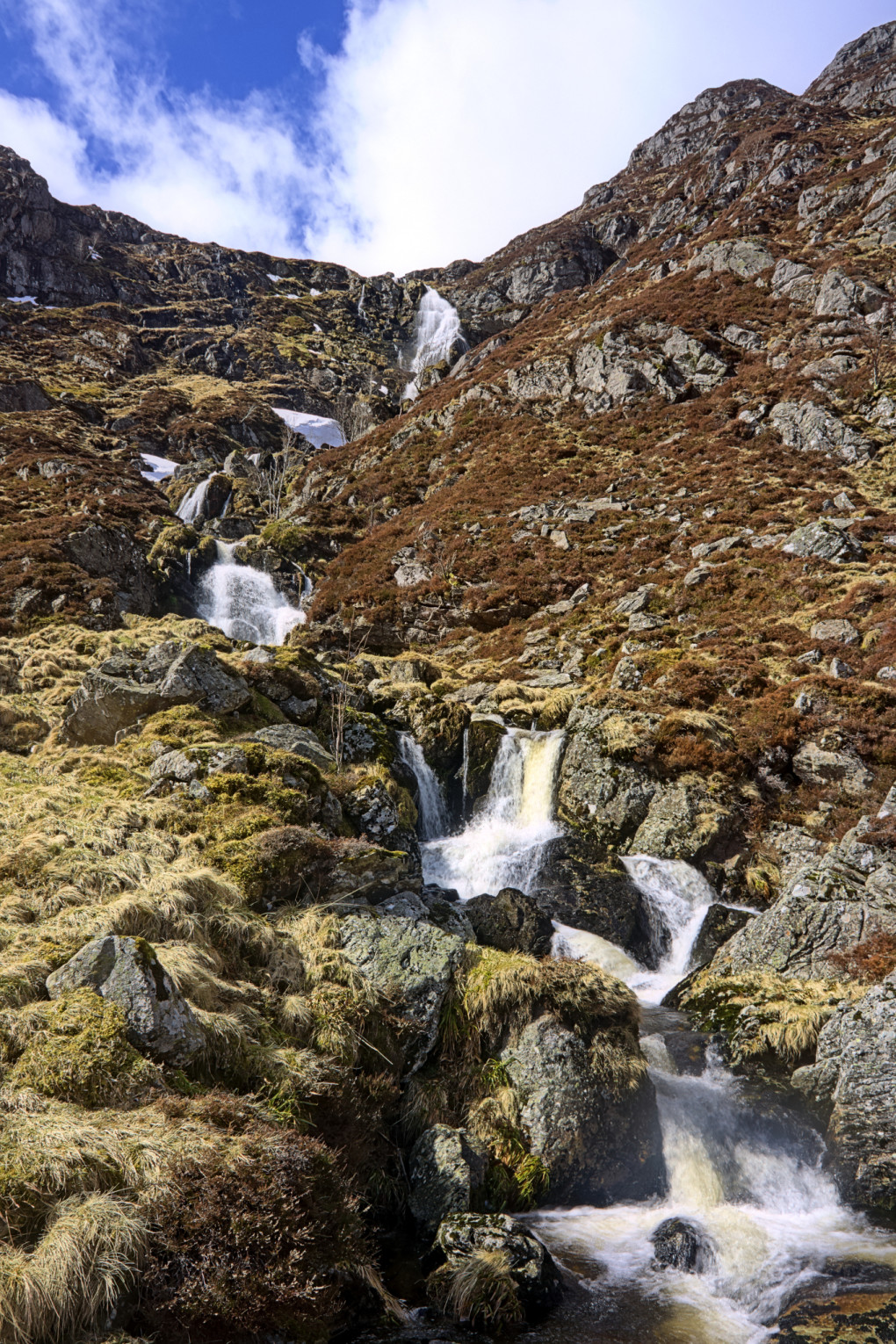 A burn cascading through several small waterfalls from the top of Corrie Fee.