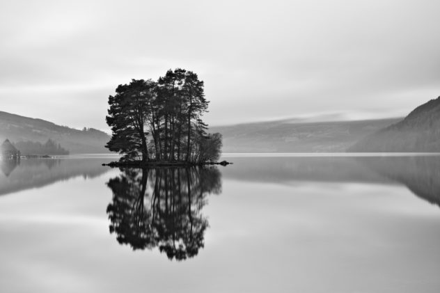 A classic view down the length of Loch Tay, hints of mist in the distant mountains and trees on the foreground island.