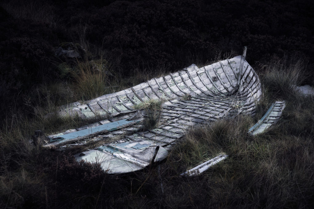 The remains of a rather dead boat resting in grass and heather at the side of Loch Tullie.