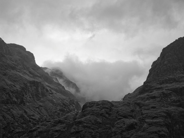 A bit of light making its way through the clouds between the bulk of Gearr Aonach and part of the craggy ridge along Beinn Fhada, two of the Three Sisters of Glencoe