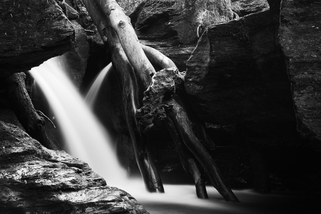 Closeup detail of the waterfall at Edinample flowing past dead fallen tree branches through the gorge
